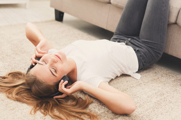 Happy young woman in headphones on floor