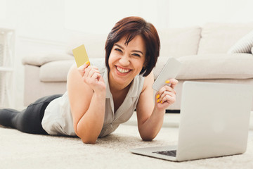 Happy young girl shopping online on floor