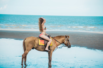 Pretty young lady riding a horse on the beach background of the sea