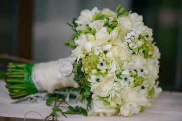 Side view of a wedding bouquet featuring ivory roses, white freesias, stephanotis blossoms mixed with greenery and wildflower, elegant floral arrangement, accessory for the bride-to-be