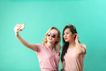 diversity, race, ethnicity, relationship concept - happy female couple, blonde caucasian and brunette Thai taking selfie with smartphone over blue background with copyspace