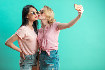 Portrait of pretty charming girls in casual outfits shooting selfie on front camera using smart phone isolated on bright violet background. Weekend vacation holiday concept