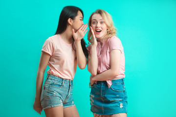 Young Asian woman telling her blonde girlfriend some secret. Two women gossiping. Excited emotional Thai girl whispering to her friend ear, turquoise studio background