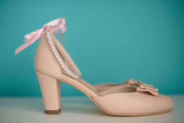 Side view of a beige leather chunky mid heel women shoes with delicate bow an pearls strap against a teal background. Elegant women footwear for formal occasion or day-to-day wear.