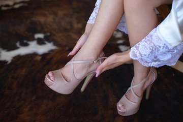Cropped shot of Caucasian young woman wearing a silky bridal kimono robe or gown, gently putting on her wedding shoes. Leg and feet detail of elegant woman, bride getting ready for her big day