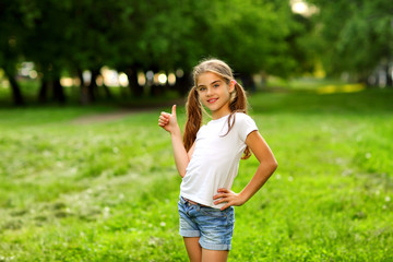 A charming girl in shorts and a t-shirt smiles in the summer against the green in the park.