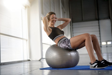 Athletic woman doing pushups with fitness ball