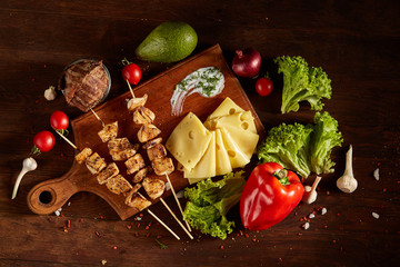Juicy pork kebab on skewers on a cutting board with fresh vegetables and cheese over a wooden background.