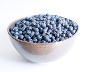 Blueberries in a cup on a white background closeup.