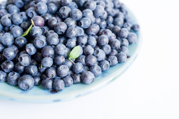 Blueberries on a blue plate on a white background close up, top view.