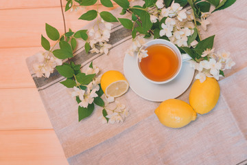 Green tea, lemon and jasmine flowers on wooden background. Top view.