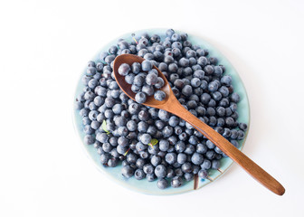 Fresh forest blueberries on a blue plate on a white background close up, top view.