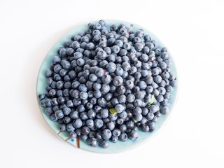 Fresh blueberries on a blue plate on a white background close up, top view.
