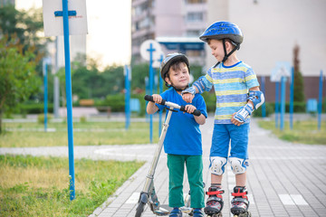 Two kid boy on roller skates and his sibling brother on scooter wrapped in park. Children wearing protection pads for safe roller skating ride. Active outdoor sport for kids