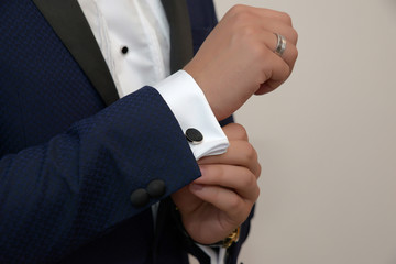Close-up shot of hands of young white Caucasian male in black tie, fixing his sleeve, signaling sprezzatura and elegance. Groom, or sophisticated businessman, or millennial male model getting ready.