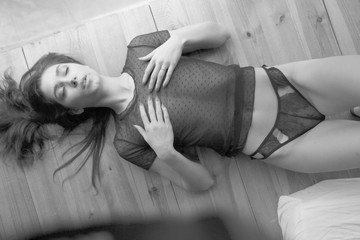 Sexy girl posing on the floor.Black white photo of the girl on the floor