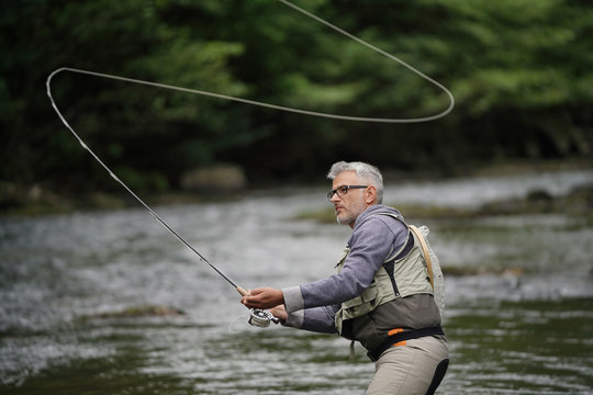 Fisherman fly-fishing in river