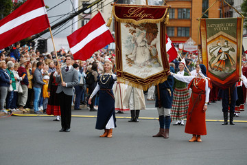 People wear traditional dress hold the national and celebration flags during the Song and Dance Celebration procession throughout the streets of Riga