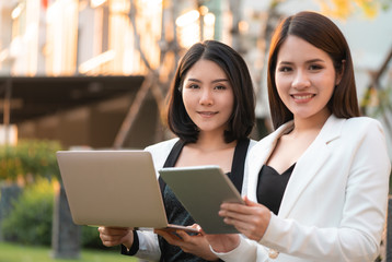 Two confidence business woman is working together in a park outdoor