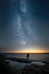 Silhouette of a man standing alone by a sea and looking at sunset and the stars of the epic milky way