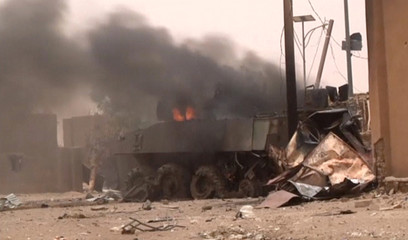 A still image taken from a video shows an armoured personnel carrier on fire after a car bomb attack in Gao