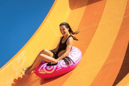 young pretty woman on the inflatable ring having fun on the orange water slide in the aqua park. Summer Vacation. Weekend on resort