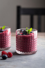 Mixed berry smoothie with mint on concrete background, close up