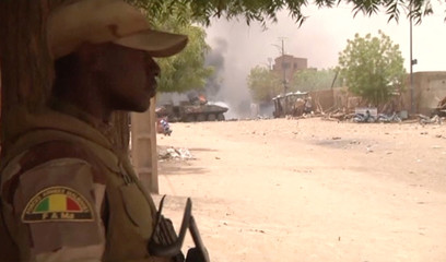 A still image taken from a video shows a Malian armed forces soldier standing guard as smoke and flames are pictured in the distance after a car bomb attack in Gao