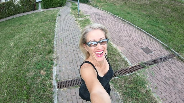 healthy lifestyle woman in sportswear running in the park holding camera for selfie. Modern woman runner on a park road. Healthy life concept. Cardio jogging training outdoor.