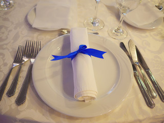 Simple table setting for formal event, elegant dining or a wedding, ready for guests, with the silverware placed in the order of use, and elegantly wrapped napkin on top of white china