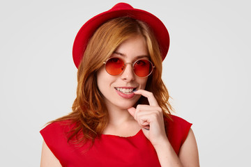 Glamour attractive young female keeps finger near mouth, smiles broadly, shows white teeth, dressed in red clothes, wears stylish sunglasses, being in high spirit after celebrating her birthday