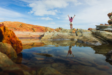 Happy young traveler woman backpacker raised arm up to sky, young woman hiking at sunrise seaside mountain