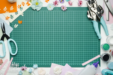 The cutting mat is surrounded by paper flowers, paper, tools and scrapbooking materials. Scrapbooking, top view, empty space in the center