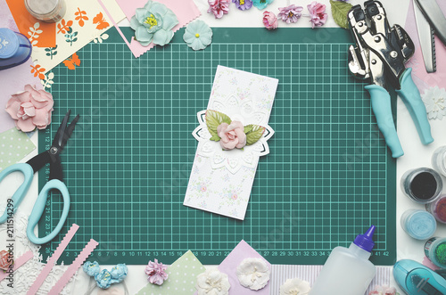 multi colored paper card on the cutting mat tools and materials for scrapbooking