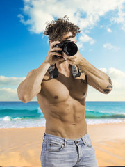 Handsome shirtless athletic male photographer with professional photo camera in hand, standing on a beach