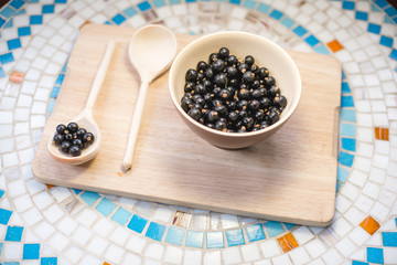 A plate of black currant and a wooden spoon on a table.