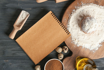 Notebook and ingredients for homemade bread on wooden table