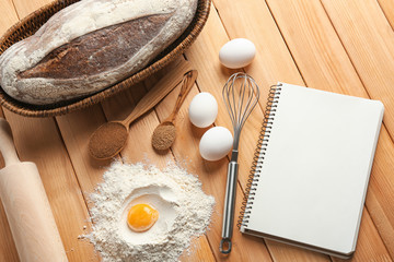 Notebook with ingredients and homemade bread on wooden background