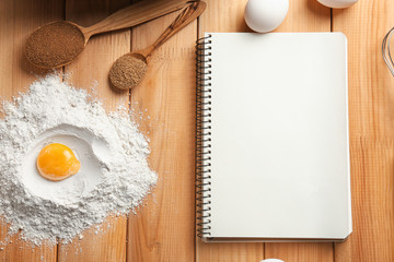 Notebook and ingredients for homemade bread on wooden background