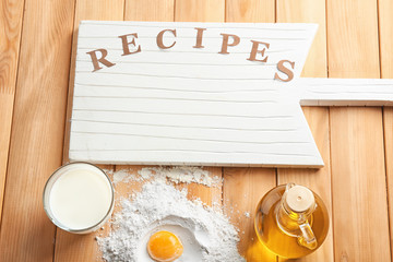 Board with word RECIPES and ingredients for homemade bread on wooden background