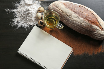 Notebook with ingredients and homemade bread on dark background