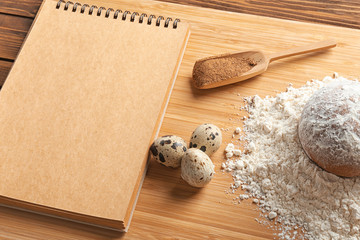 Notebook and ingredients for homemade bread on wooden board