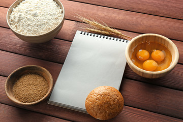Notebook and products for making bread on wooden background