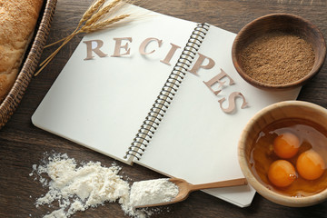 Notebook with word RECIPES and ingredients for making bread on table