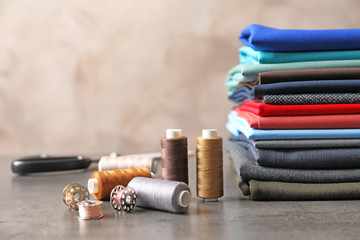 Bobbins with threads and stack of colorful fabrics on table. Tailoring accessories