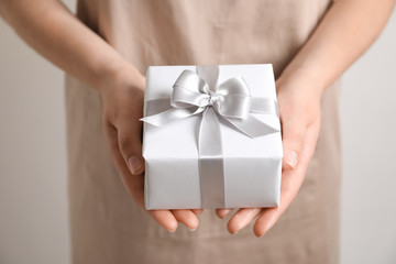 Woman holding gift box on light background