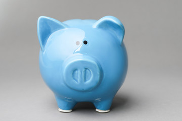 Cute blue piggy bank on gray background