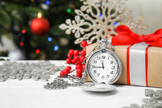 Pocket watch, gift and festive decor on table. Christmas countdown
