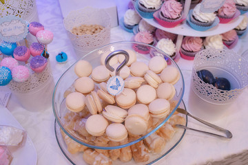 Top view of glass cake stand with tasty pastel French macarons, bite size profiteroles and pink meringues, surrounded by plates full of cake pops and cupcakes at  at a typical dessert bar for parties