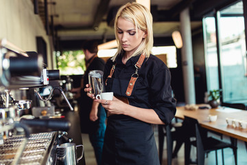 Procedure of making fresh coffee. Professional baristas pouring milk into cup of espresso coffee.